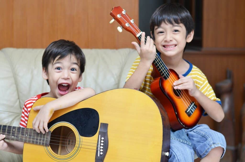 two happy kids playing guitar and uke