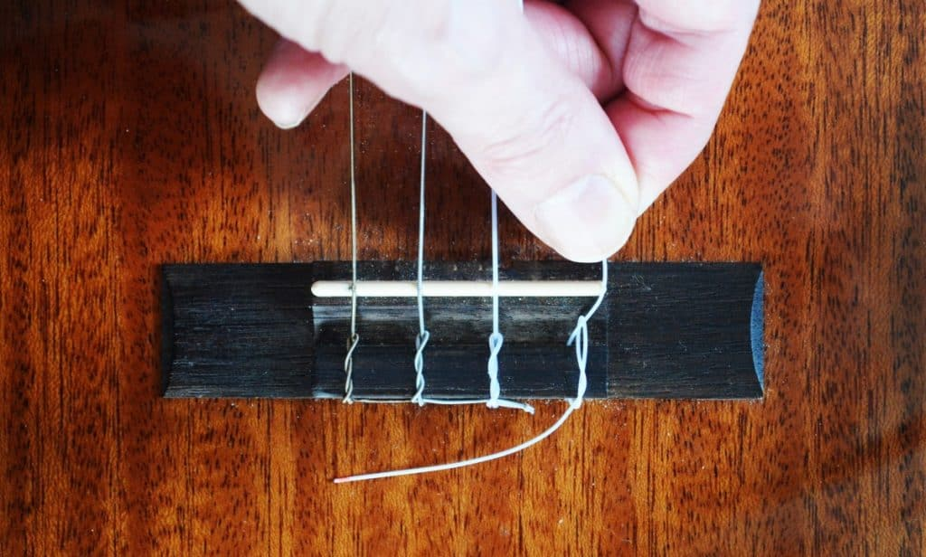 Step 6: The string should now be slipped under and over again to form a figure eight, rather than the existing 'O' shape.