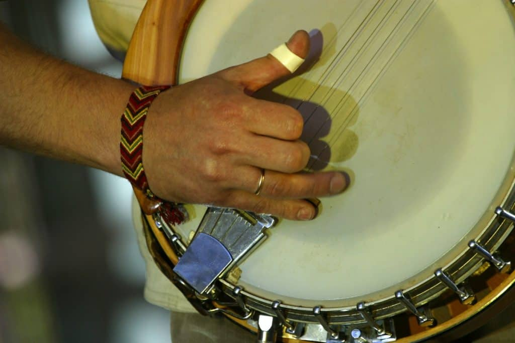 a man with a bandage on his finger still pursue to play the banjo